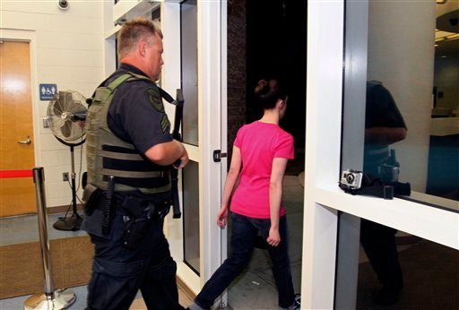 Casey Anthony walks out of the Orange County Jail escorted by a sheriff's deputy during her release in Orlando, Fla., early July 17, 2011. Anthony was acquitted last week of murder in the death of her daughter, Caylee. (AP Photo/Red Huber, Pool)