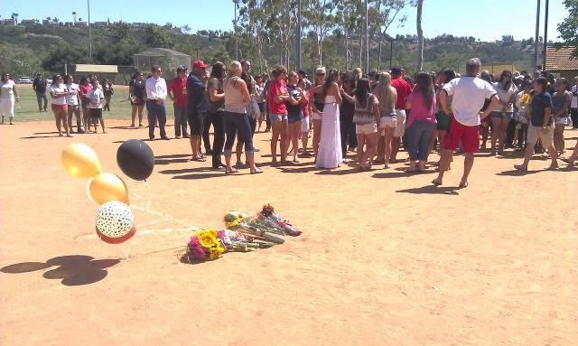 Friends put flowers on a pitcher's mound to honor 18-year-old Briana Williams. Williams was found dead along with her mother at their Rancho Penasquitos home Monday.