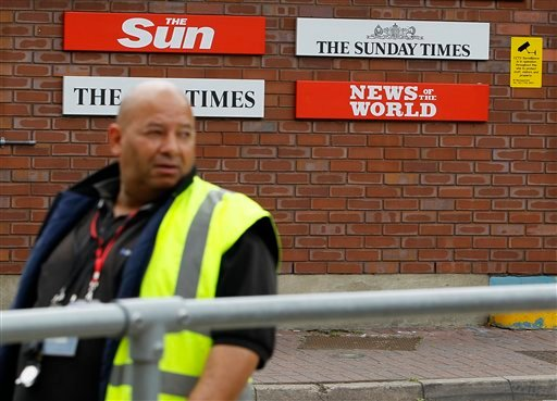 A security guard keeps watch at News International in Wapping, London, Thursday, July 14, 2011.