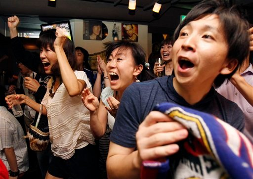 Fans cheer the Japanese team playing with the United States in their Women's Soccer World Cup final match, at the Rooney2008 sports bar in Tokyo, Monday morning, July 18, 2011.