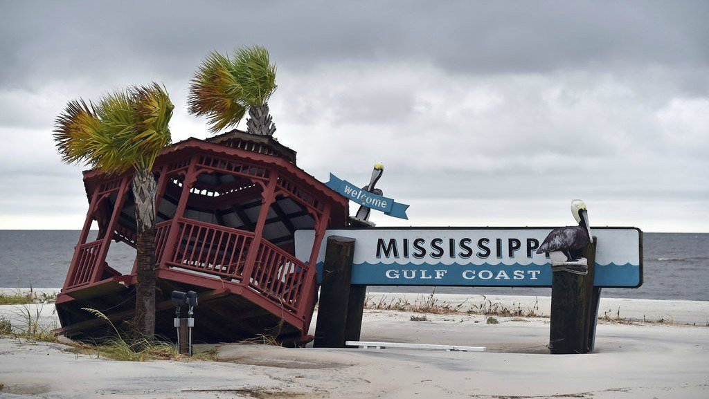 A gazebo is blown over the Mississippi Gulf Coast welcome sign near the intersection of Hewes Avenue and U.S. 90 in Gulfport, Miss., Sunday, Oct. 8, 2017, after Hurricane Nate made landfall on the Gulf Coast. (Justin Sellers/The Clarion-Ledger via AP)