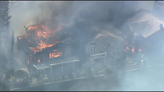 Homes burn as fire roars through Anaheim Hills