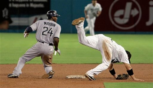Florida Marlins shortstop Omar Infante lands after jumping over San Diego Padres' Cameron Maybin and throwing to first in the seventh inning of a baseball game in Miami July 19, 2011. (AP Photo/J Pat Carter)