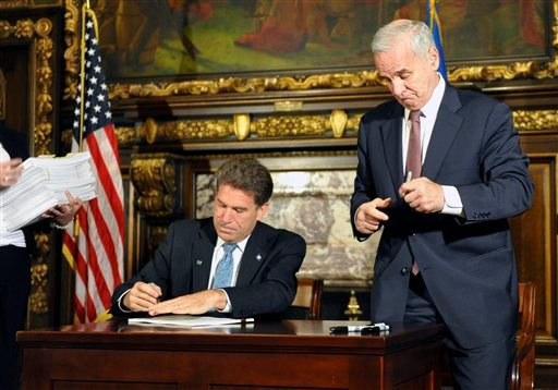 Minnesota Gov. Mark Dayton closes his pen as Secretary of State Mark Ritchie, left, signs the final bill of the budget bill which ends the government shutdown July 20, 2011 in St. Paul, Minn. (AP Photo/Jim Mone)