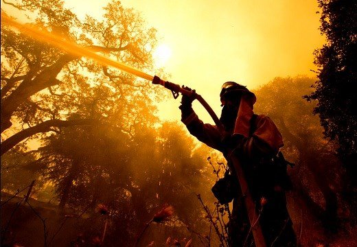 Napa County firefighter Jason Sheumann sprays water on a home as he battles flames from a wildfire.