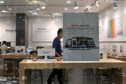 A shopkeeper dressed as an Apple store employee looks out from a window of a shop masquerading as a bona fide Apple store in downtown Kunming, in southwest China's Yunnan province, Thursday, July 21, 2011.