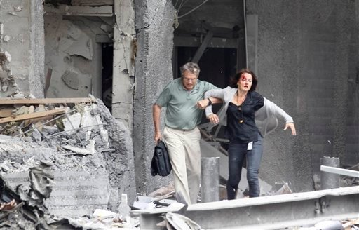 An injured woman is assisted from a damaged building in Oslo, Friday July 22, 2011, after an explosion rocked the capital.