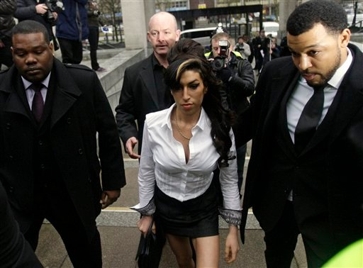 In this Jan. 20, 2010 file photo, British singer Amy Winehouse, center, arrives at Magistrates Court in Milton Keynes, England. Winehouse, the beehived soul-jazz diva whose self-destructive habits overshadowed a distinctive musical talent, was found dead