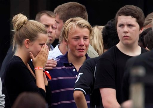 Unidentified survivors from the shooting at an island youth retreat react outside a hotel where survivors were being reunited with their families in Sundvolden, Norway, Saturday, July 23, 2011.