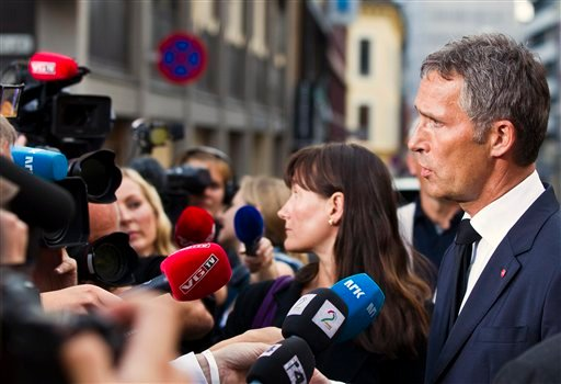 Norway's Prime Minister Jens Stoltenberg, right, addresses members of the media after inspecting the damage caused by Friday's explosion near the government building, Oslo, Saturday, July 23, 2011. (AP)