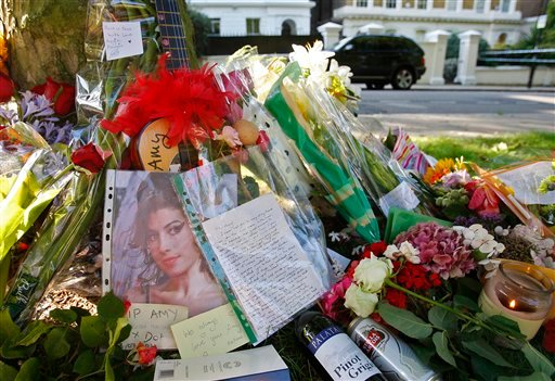 An unidentified woman leaves a floral tribute outside the residence of singer Amy Winehouse in Camden Square, north London, Sunday, July 24, 2011. (AP)