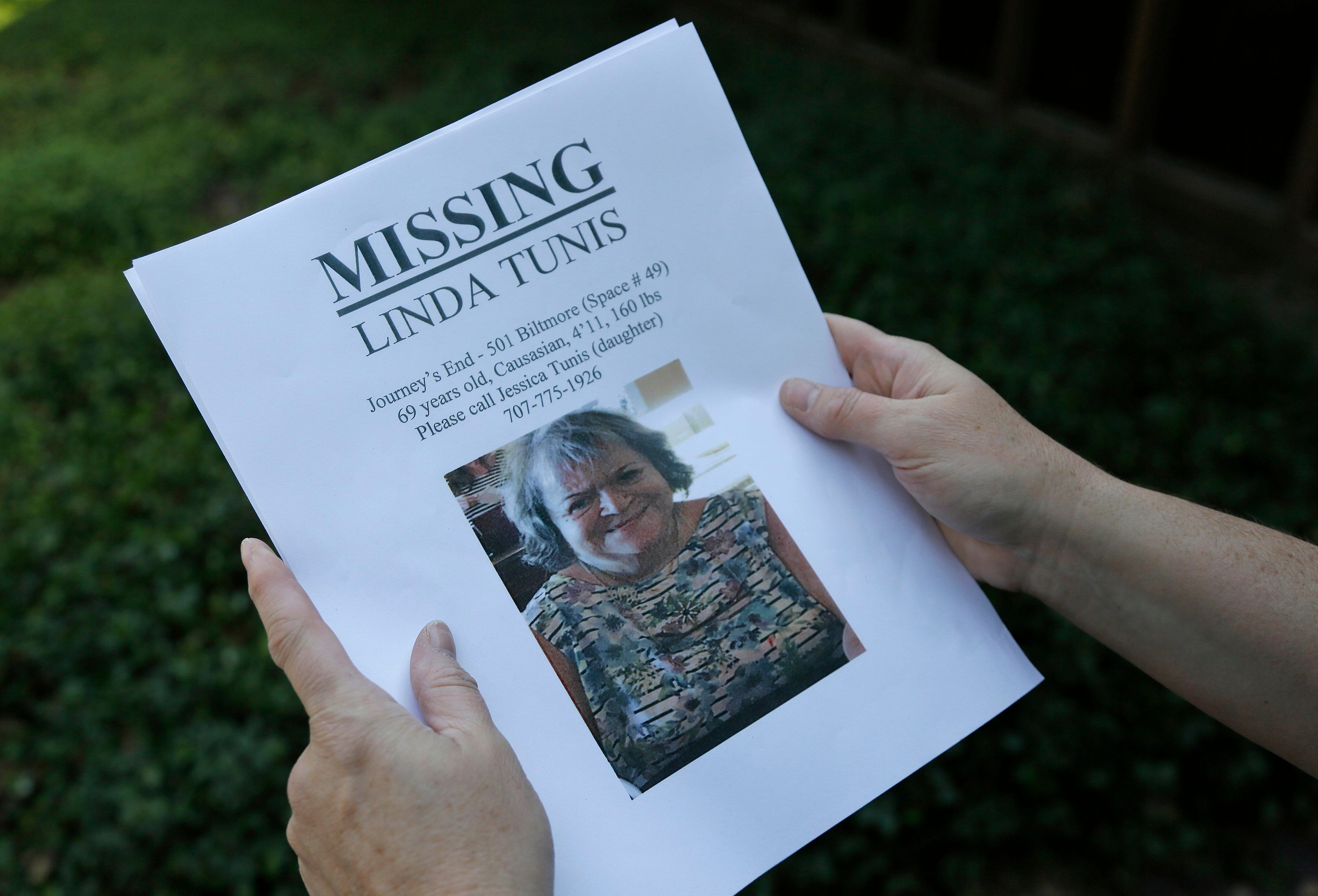 Jessica Tunis stands outside a Red Cross evacuation center and holds a flyer about her missing mother Wednesday, Oct. 11, 2017, in Santa Rosa, Calif. Tunis is searching for her missing mother, Linda Tunis, who was living at a mobile home park when wildfir
