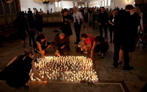 People light candles after a service at Oslo Cathedral in the aftermath of the attacks on Norway's government headquarters and a youth retreat in Oslo, Sunday, July 24, 2011. (AP)