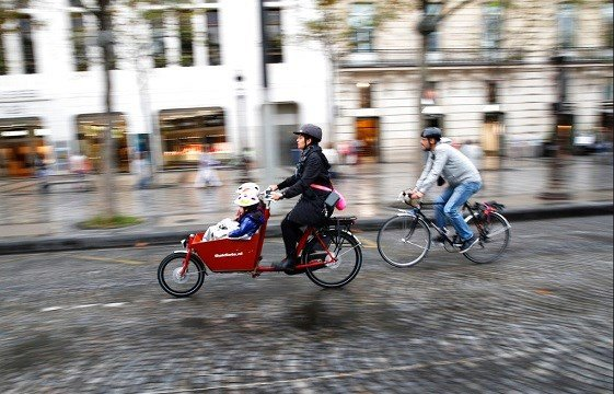 "A woman and a man ride their bicycles on the Champs Elysees avenue during the ""day without cars"", in Paris."