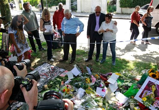 Mitch Winehouse, center blue shirt, Amy Winehouse 's father, accompanied by Janis, Amy's mother, seen right white shirt and other friends, looks at flowers placed by mourners in Camden Square outside the house of Amy Winehouse following her death.