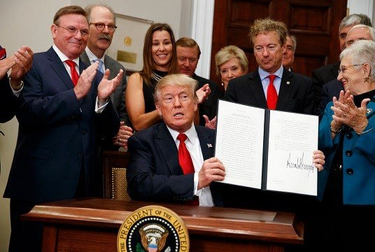 President Donald Trump shows an executive order on health care that he signed in the Roosevelt Room of the White House.