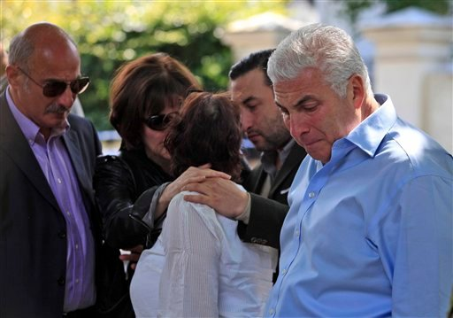 Mitch Winehouse, right, Amy Winehouse 's father, accompanied by Janis, Amy's mother, background , comforted by friends, looks at flowers left by mourners in Camden Square outside the house of Amy Winehouse following her death, in Camden, northern London.