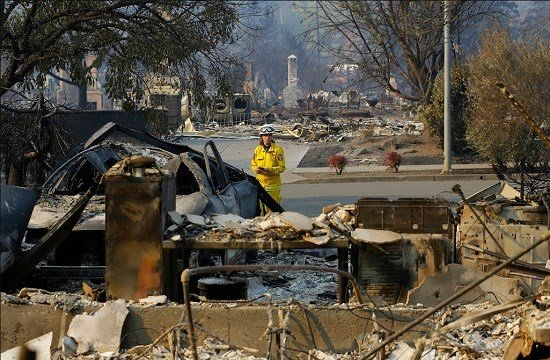 Cal Fire forester Kim Sone inspects damage at homes destroyed by fires in Santa Rosa, Calif.