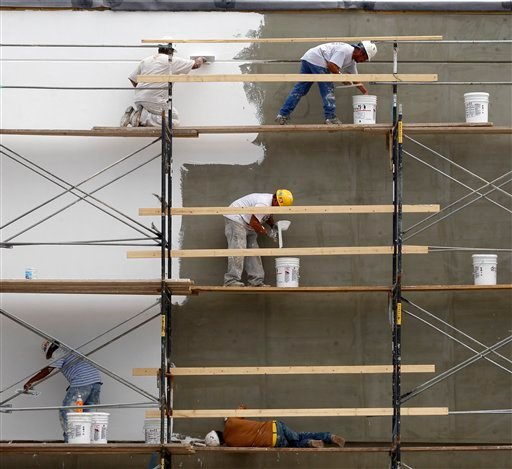 In this July 15, 2011 photo, workers put a new surface on the outside of a retail store at a shopping plaza in Mayfield Hts., Ohio. A private research group is reporting that U.S. consumers' confidence rose slightly in July. (AP)