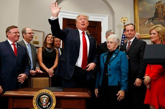 President Donald Trump waves after signing an executive order on health care in the Roosevelt Room of the White House.