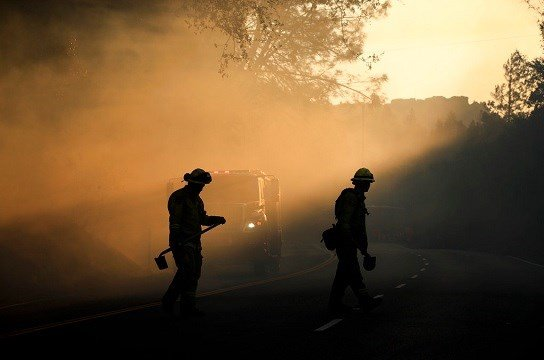 Two firefighters watch for spot fires Friday, Oct. 13, 2017, near Calistoga, Calif.