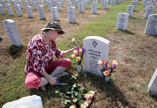 In this photo taken Saturday, July 23, 2011, in North Little Rock, Ark., Janet Long, mother of slain Army Pvt. William Andrew Long, places flowers on her son's grave.