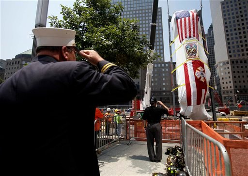 Firefighters and other guests salute as the Fire Department of New York's Ladder Company 3 fire truck is lowered by crane into the National September 11 Memorial Museum in New York, Wednesday, July 20, 2011.