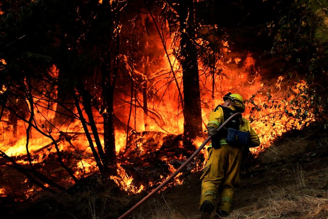 A firefighter carries a water hose to put out a fire during along the Highway 29 Friday, Oct. 13, 2017, near Calistoga, Calif.  (AP Photo/Jae C. Hong)