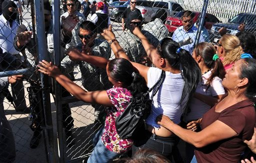 Inmate family members ram the state prison gates demanding information in Ciudad Juarez, Mexico, Tuesday July 26, 2011.