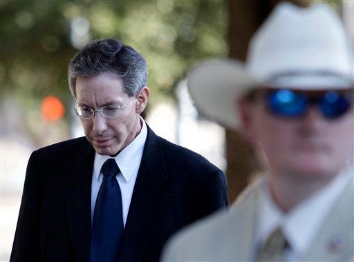 A law enforcement official stands by as Polygamist sect leader Warren Jeffs, left, arrives at the Tom Green County Courthouse July 28, 2011, in San Angelo, Texas. (AP Photo/Tony Gutierrez)