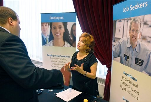 In this July 21, 2011 photo, Donna Ciora, an employment specialist with Express Employment Professionals, right, talks with people attending the Pittsburgh Career Fair, in Pittsburgh. (AP Photo/Keith Srakocic)