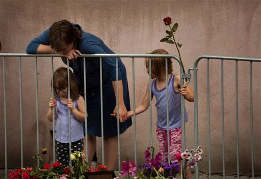 A woman with her two daughters looks at tributes outside the Oslo Cathedral in Oslo, in memory of the victims of Friday's bomb attack and shooting rampage, Norway, Thursday, July 28, 2011.