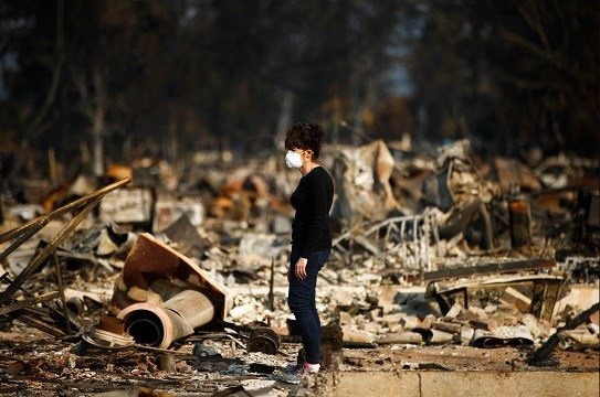 Karen Curzon stands in what remains of her home, which was destroyed by a wildfire in the Coffey Park neighborhood.