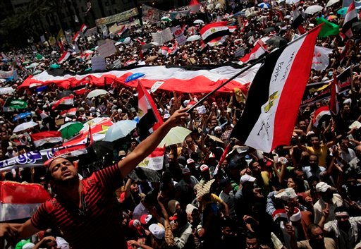 """A protester waves an Egyptian flag that reads """"We Love Egypt"""" during a demonstration after Friday prayers in Tahrir Square where many have set up protest tent camps in the main city square in Cairo, Egypt, Friday July 29, 2011. (AP)"""