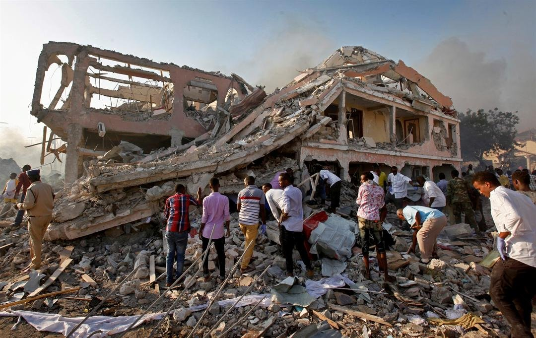 Somalis gather and search for survivors by destroyed buildings at the scene of a blast in the capital Mogadishu, Somalia Saturday, Oct. 14, 2017.  (AP Photo/Farah Abdi Warsameh)