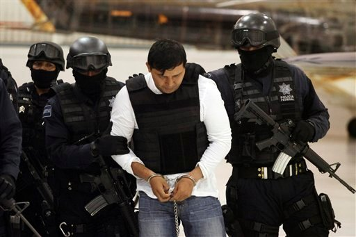 "Federal Police agents escort Jesus Enrique Aguilar, alias ""El Mamito"", to his presentation to the media in Mexico City, Monday July 4, 2011. (AP)"