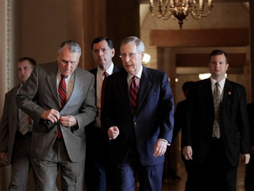 As the debt crisis continues Senate Minority Leader, Republican Mitch McConnell of Kentucky, walks to the Senate floor for a vote on a solution crafted by Senate Majority Leader Harry Reid, D-Nev, not shown, at the Capitol in Washington, Sunday, July 31.