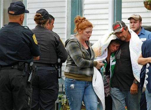 New Hampshire State Police officers watch as a woman identified by the NH Attorney General's office as Celina Cass's mother, under blanket, is escorted from the family home in Stewartstown, N.H., Wednesday, July 27, 2011.