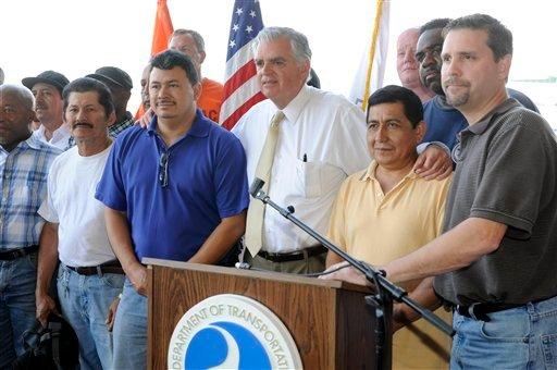 U.S. Transportation Secretary Ray LaHood, center, poses with tradesmen after a news conference to discuss the interruption of federal funding for airport construction projects and contractors at LaGuardia Airport in New York, Monday, August 1, 2011.