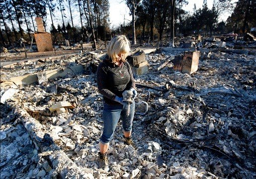 Debbie Wolfe dumps ashes from a pot she found in the burned ruins of her home Tuesday, Oct. 17, 2017, in Santa Rosa, Calif.