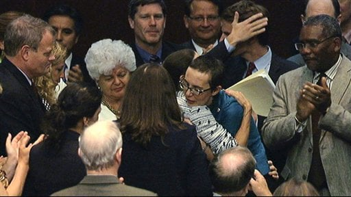 In this image from House Television, Rep. Gabrielle Giffords, D-Ariz., center, gets a hug as she appears on the floor of the House of Representatives.