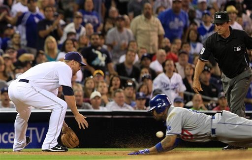 Los Angeles Dodgers' Matt Kemp goes in head-first with a triple as San Diego Padres third baseman Chase Headley takes in a wide throw in the eighth inning of a baseball game Aug. 1, 2011, in San Diego. The umpire is Phil Cuzzi. (AP Photo/Lenny Ignelzi)