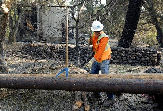A Pacific Gas & Electric worker replaces power poles destroyed by wildfires in Glen Ellen, Calif.
