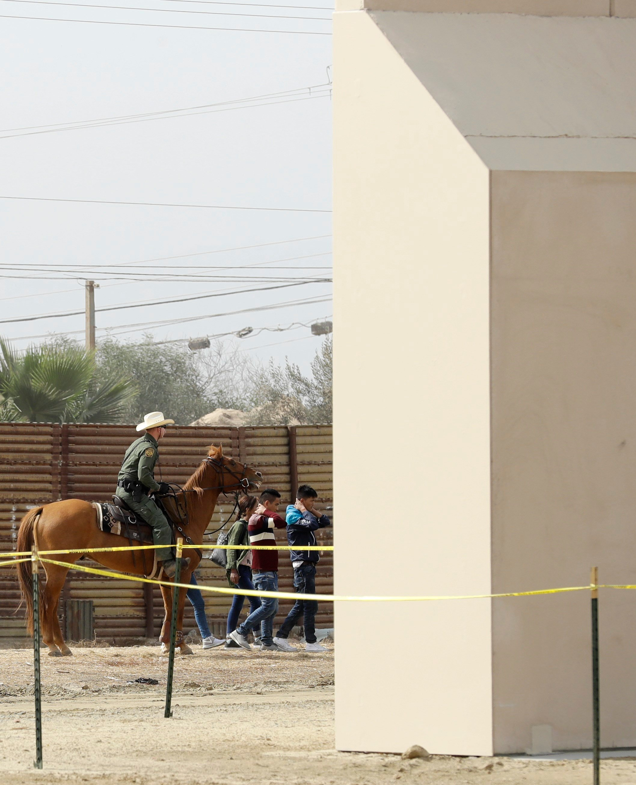 A group of people are detained by Border Patrol agents on horseback after crossing crossing the border illegally from Tijuana, Mexico, near prototypes for a border wall, right, are being constructed Thursday, Oct. 19, 2017, in San Diego.