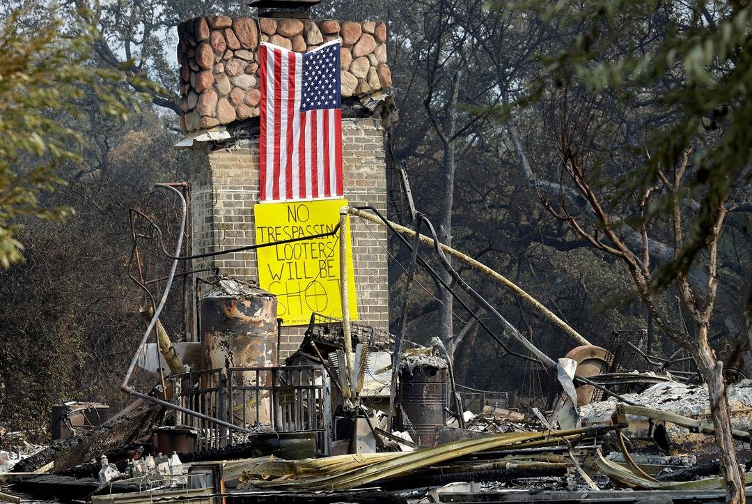 A sign on the chimney of a home warns looters Wednesday, Oct. 18, 2017, after it was destroyed by wildfires in Glen Ellen, Calif. California fire officials have reported significant progress on containing wildfires that have ravaged parts of Northern Cali