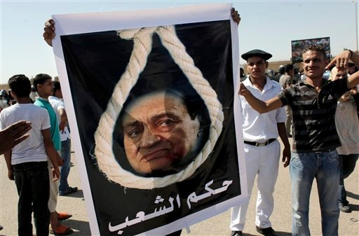 "An anti-Mubarak protester carries a poster with a picture of Mubarak and a hanging robe with Arabic that reads ""The people's judgment"", outside the Police Military Academy complex in Cairo, Egypt Wednesday, Aug. 3, 2011."