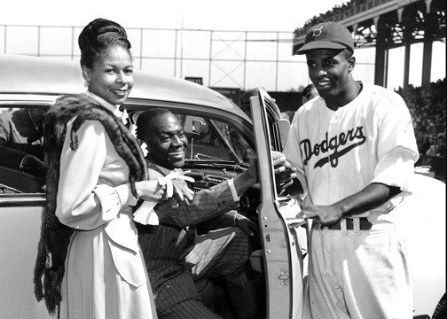 Brooklyn Dodgers baseball player Jackie Robinson, right, receives the keys to a car from tap dancer Bill Bojangles Robinson as Jackie Robinson's wife, Rachel, looks on at Ebbets Field in New York.