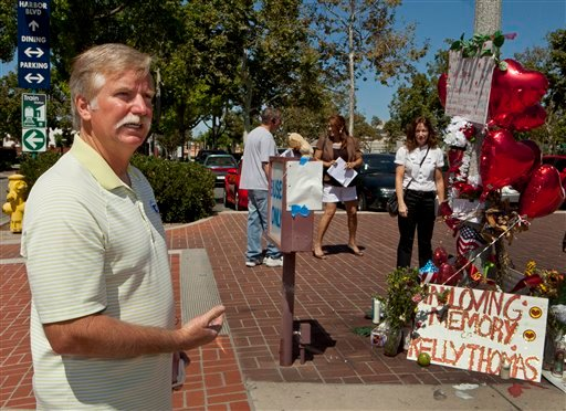 Ron Thomas, the father of victim, Kelly Thomas, stands next to a memorial for his son on Aug. 3, 2011, at the Fullerton Transportation Center in Fullerton, Calif. (AP Photo/Damian Dovarganes)