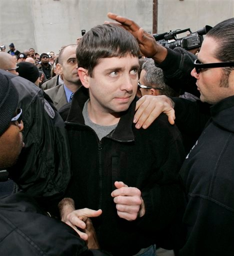 In this Jan. 2, 2007, file photo, Michael Hunter Jr., center, shakes hands with a fellow officer as he and six other New Orleans police officers turn themselves in at the city jail in New Orleans.
