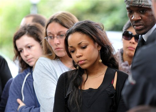 Singer Dionne Bromfield, goddaughter of Amy Winehouse, views tributes outside the late singer's north London home, Tuesday, July 26, 2011. (AP)